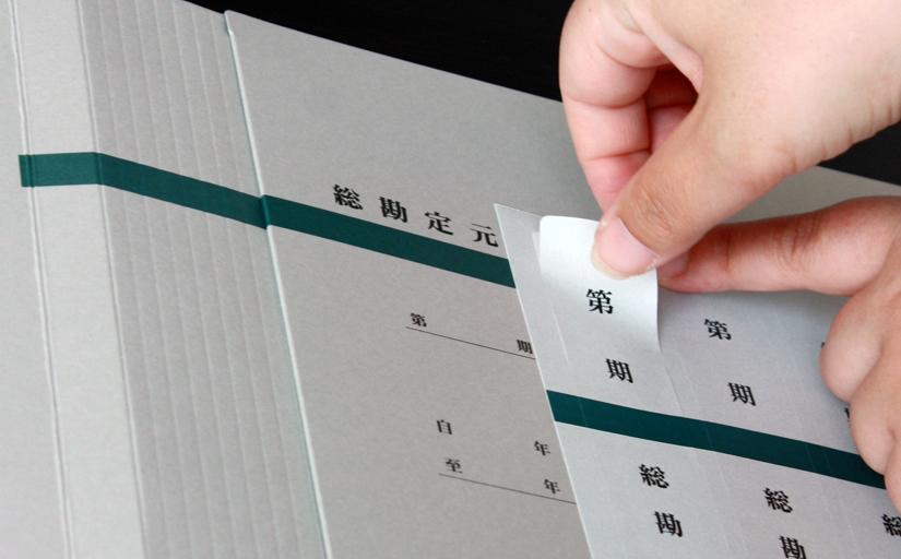 背幅自由自在・総勘定元帳の背表紙に張るタイトルシールをはがす画像